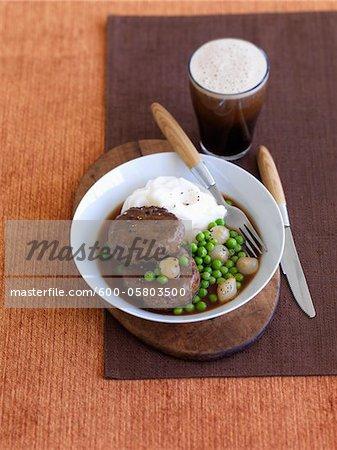 Rindfleisch Patty, Erbsen, Kartoffelpüree und Glas Bier