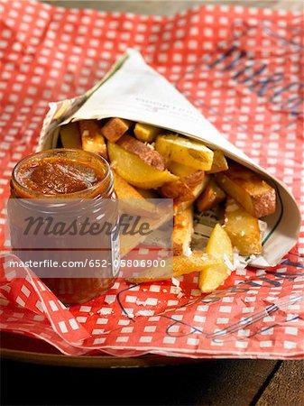 Frites dans un cône de journal avec chutney de céleri et ketchup