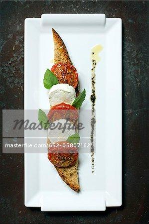 Tomates grillées, fromage de chèvre frais et d'herbes sur toast