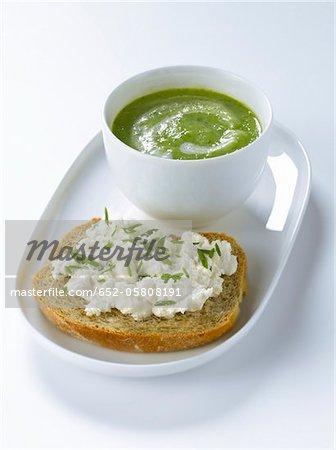 Creme-Zucchini-Suppe, eine Scheibe Brot Leinsamen mit Ziegenmilch Käse und Schnittlauch
