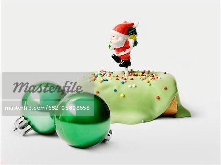 Gâteau de Noël pistache journaux individuels avec un père Noël figurine et vert sapin de Noël boules