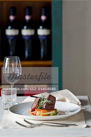 Assiette de steak de boeuf au romarin et légumes dans un bar à vin
