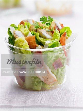 Salade César dans un récipient en plastique