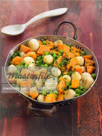 Patates douces, des pois et des oignons cuits dans un wok