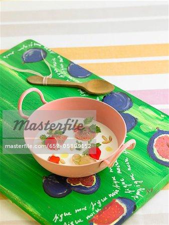 Crème d'ail avec les noix de pin, figues, raisins et cerfeuil