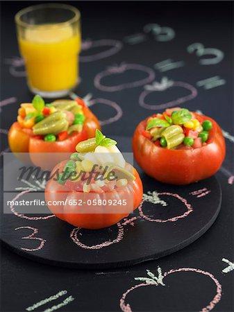 Tomates crues farcies aux pois, poivrons rouges et le maïs sucré