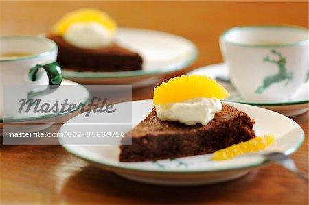Slice of chocolate cake with cream and fresh orange