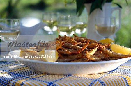 D'éperlans frits avec des quartiers de citron et de verres de vin blanc