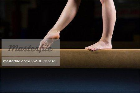 Female gymnast on balance beam, low section
