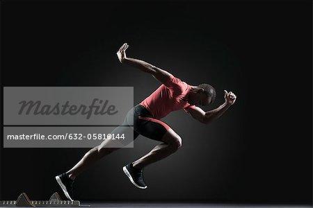 Male athlete leaving starting block