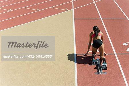 Frau kauerte in Ausgangsposition auf der Laufstrecke, Rückansicht
