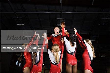 Team of female gymnasts celebrating victory together