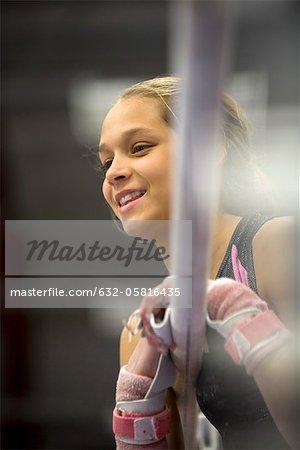 Female gymnast leaning against horizontal bar, portrait