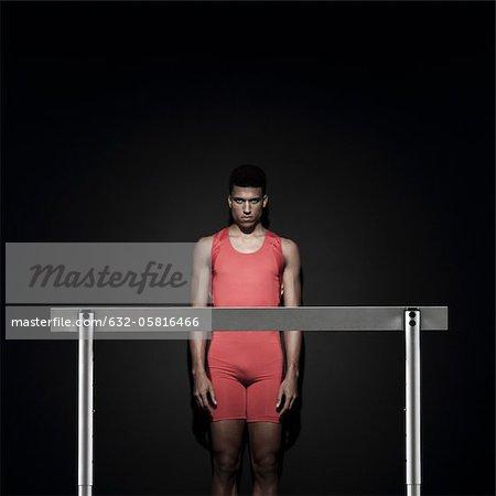 Male athlete standing behind hurdle