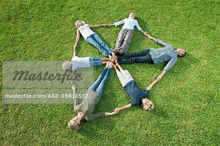 Menschen auf Gras bilden Form des Schildes