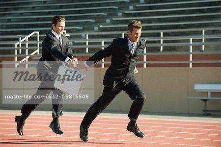 Geschäftsleute im Staffellauf, Übergabe Aktenkoffer