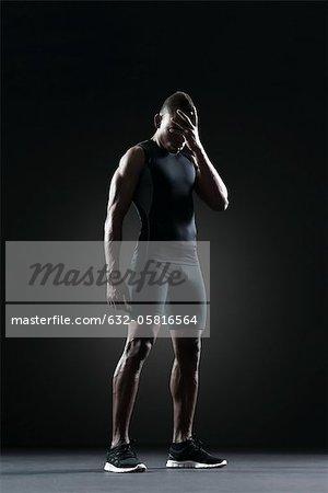 Athlète masculin avec main couvrant les yeux
