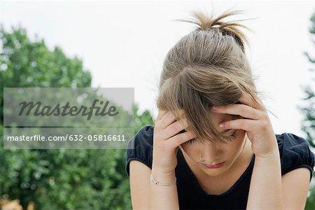 Jeune femme bouleversée tenant tête et regardant vers le bas