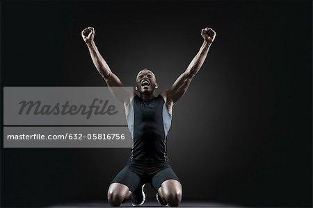 Athlète masculin criant les bras levés