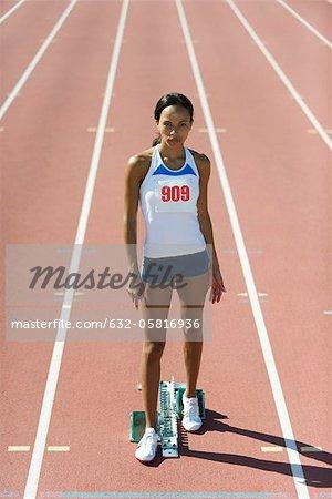 Female runner standing at starting line, portrait