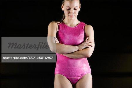 Gymnaste féminine debout avec les bras croisés sur la poitrine, regardant vers le bas dans la déception