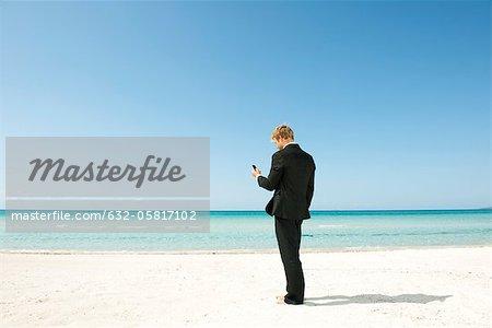 Businessman using cell phone on beach