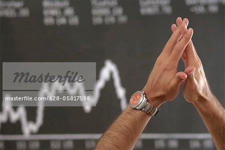 Hände eines Mannes vor einem Aktienkurs