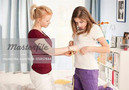 Teenage girl measuring waist of her friend