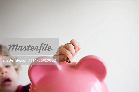 Little boy putting money in piggy bank