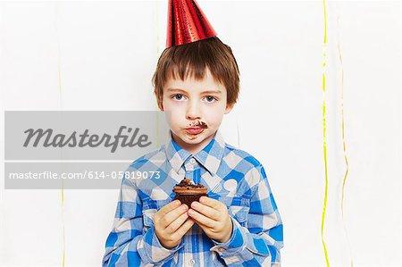 Garçon avec cupcake autour de sa bouche