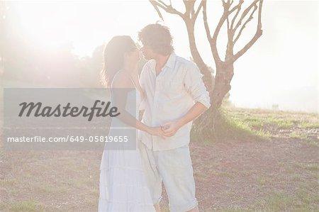 Couple s'embrassant dans le champ
