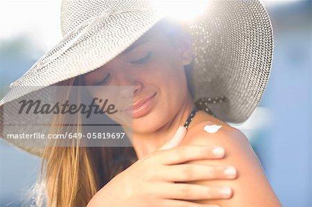 Teenage girl applying sunscreen outdoors