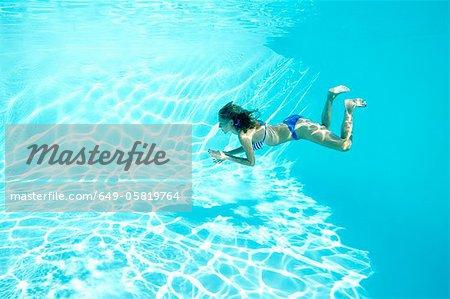Femme en bikini, nager dans la piscine