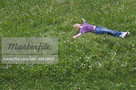 Femme souriante pose dans l'herbe
