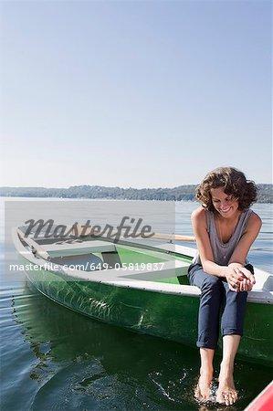 Femme, balançant les pieds du bateau dans le lac