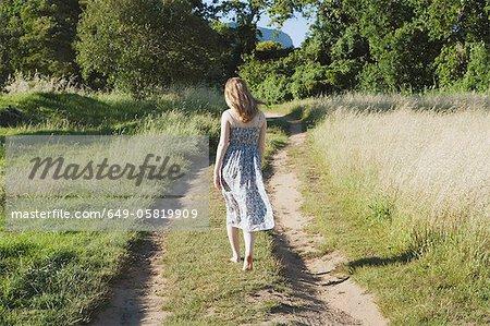 Adolescente marche sur chemin de terre