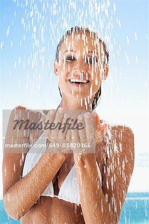Woman splashing in swimming pool