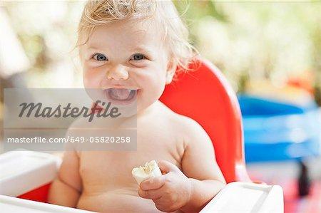 Lachend Kleinkind Essen im Hochstuhl