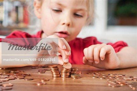 Mädchen spielen mit ein paar Cent am Tisch