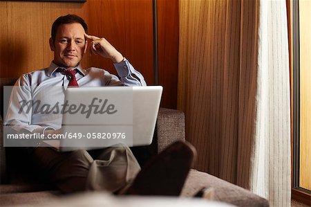 Kaufmann mit Laptop im Hotelzimmer