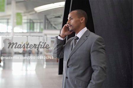 Kaufmann mit Handy in Flughafen