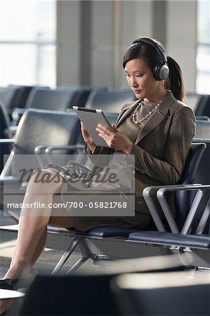 Geschäftsfrau mit Tablet-PC in Flughafen
