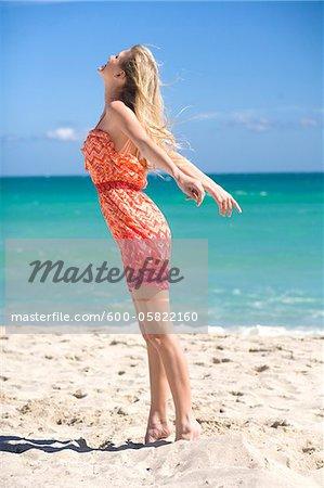 Femme debout sur la plage, se sentant la brise
