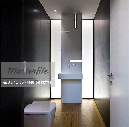 Salle de bains moderne avec un éclairage dramatique et plancher en bois dans des maison, Verlaine, Tel Aviv, Israël. Architectes : Pitsou Kedem