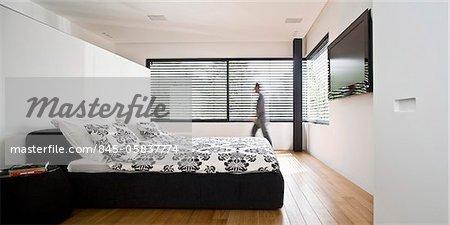 Man walks across bedroom in contrasting black and white, UP House, Hertzelia, Tel Aviv, Israel. Architects: Pitsou Kedem