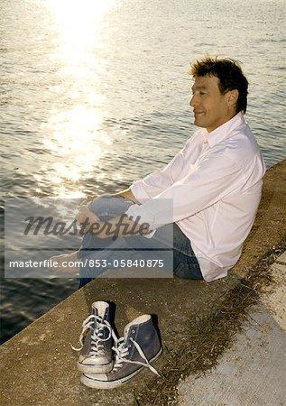 Homme assis sur le bord de l'eau