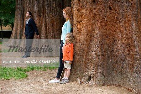 Mère et fille adossée à arbre, père permanent distinct en arrière-plan