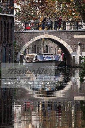Une péniche de tourisme sous un pont sur le Canal Oudegracht dans la ville néerlandaise d'Utrecht, Province d'Utrecht, Pays-Bas, Europe
