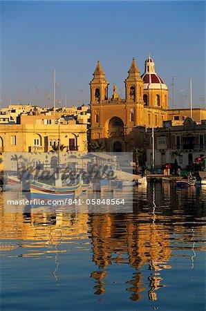 Harbour with Luzzu fishing boats and Marsaxlokk Parish Church at sunrise, Marsaxlokk, Malta, Mediterranean, Europe