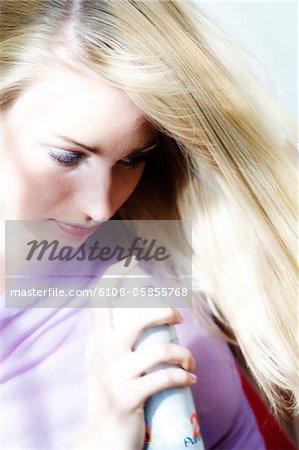 Porträt einer jungen Frau mit Haarspray